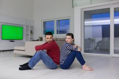 Young couple sitting with back to each other on floor. Cheerful young couple sitting with back to each other on floor at home Stock Photo