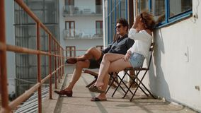 Young couple sitting in the balcony stock footage