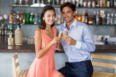 Young couple sitting at bar counter and toasting a glasses of champagne Royalty Free Stock Photography