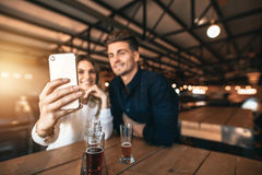 Young couple sitting in the bar and taking a selfie Royalty Free Stock Photography