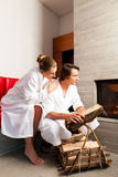 Young couple sitting in bathrobe for fire Royalty Free Stock Images