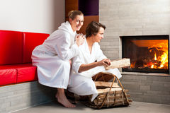 Young couple sitting in bathrobe for fire Stock Photography