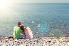 Young couple sitting on the beach Stock Image