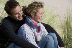 Young couple sitting on beach stock image