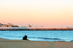 Young couple sitting on beach in front of calm sea at sunset. Boy and girl sitting on beach at sunset kissing in barcelona Royalty Free Stock Photography