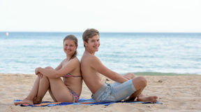 Young couple sitting on the beach Stock Images
