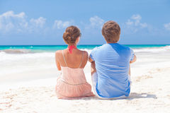 Young couple sitting on the beach looking on the Stock Photo