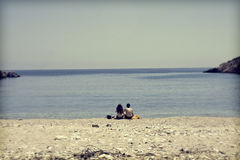 Young couple sitting on the beach and looking at sea Royalty Free Stock Photos