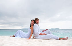 Young couple sitting on the beach near the seaside Royalty Free Stock Photo
