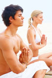 Young couple sitting at the beach practicing yoga Stock Images