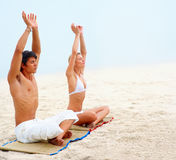 Young couple sitting at the beach practicing yoga Royalty Free Stock Photos