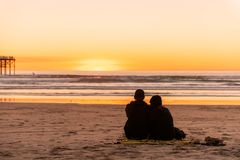 Young couple sitting on the beach watching golden sunset royalty free stock photos