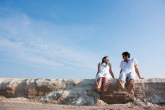 Young couple sitting on the beach with your feet and laughing Royalty Free Stock Photo