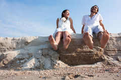 Young couple sitting on the beach with your feet and laughing Stock Photo