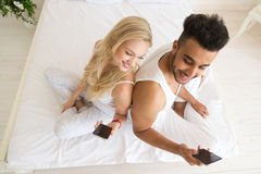 Young Couple Sitting In Bed, Happy Smile Hispanic Man And Woman Using Cell Smart Phone Royalty Free Stock Image