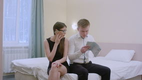 Young couple sitting on bed in living room, man planning vocation trip using a map, woman having a phone call. Professional shot in 4K resolution. You can use stock footage