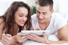 Young couple sitting on the bed using tablet pc Royalty Free Stock Photography