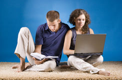 Young couple sitting on beige carpet Stock Photos
