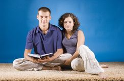 Young couple sitting on beige carpet Stock Image