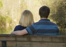 Young couple sitting on a bench. This young couple is sitting on a bench at the edge of a creek in the golden hours of evening royalty free stock images