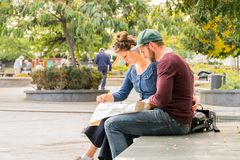 Young couple sitting on a bench in Budapest looking at a city map to find direction. Royalty Free Stock Image