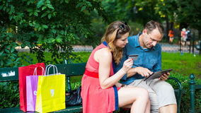 Young couple sitting on a bench with colorful shopping bags and tablet. Royalty Free Stock Photography