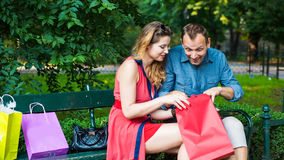 Young couple sitting on a bench with colorful shopping bags and tablet. Royalty Free Stock Photos