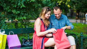 Young couple sitting on a bench with colorful shopping bags and tablet. Stock Photo
