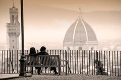 Young couple sitting on a bench, in front of Florence cityscape panorama stock images