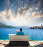 Young couple is sitting on the bench in front of sea stock photo