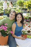 Young couple sitting on bench in garden centre Stock Image