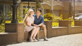 Young couple sitting on bench and holding hands, guy in love hugging girlfriend. Stock video royalty free stock photography