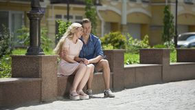 Young couple sitting on bench and holding hands, guy in love hugging girlfriend. Stock footage stock footage