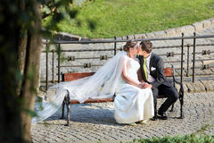 Young couple sitting on a bench and kissing in a hug Stock Photos