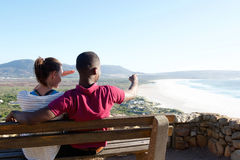 Young couple sitting on a bench and looking at sea Stock Photo