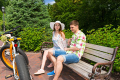 Young couple sitting on bench near bikes in park Royalty Free Stock Image