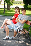 Young couple sitting on bench in park Stock Photos