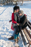 Young couple sitting on a bench in a park in Winter Royalty Free Stock Photography