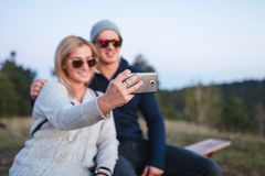 Young couple taking selfie at mountain sunset stock photos