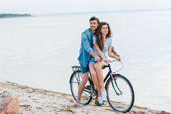 young couple sitting on bicycle on beach royalty free stock photo