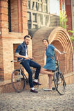 Young couple sitting on a bicycle opposite city Stock Photography