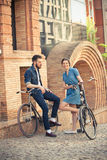 Young couple sitting on a bicycle opposite city Royalty Free Stock Image