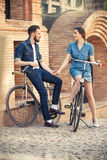 Young couple sitting on a bicycle opposite city Royalty Free Stock Photo