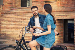 Young couple sitting on a bicycle opposite city Royalty Free Stock Photography