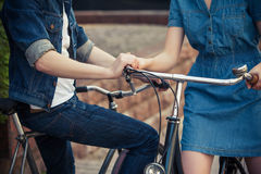Young couple sitting on a bicycle opposite the Royalty Free Stock Images