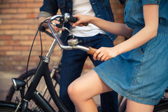 Young couple sitting on a bicycle opposite the Stock Photo
