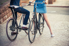 Young couple sitting on a bicycle opposite the Stock Images