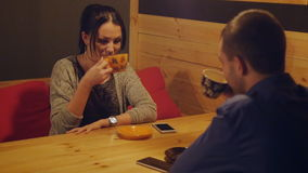 Young couple sitting in a cafe at a table drinking coffee and talking. Girl face smiling. Two lovers enjoy the evening stock footage