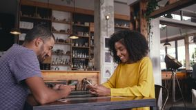 Young couple sitting in cafe using their smart phone stock footage