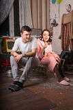 Young Couple Sitting on Cage at Messy Room stock images